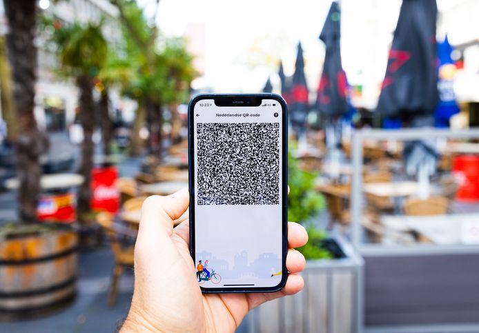 Een mobiele telefoon met de QR-code via de app CoronaCheck, vanaf zaterdag verplicht voor bezoekers van de horeca, bioscoop et cetera.