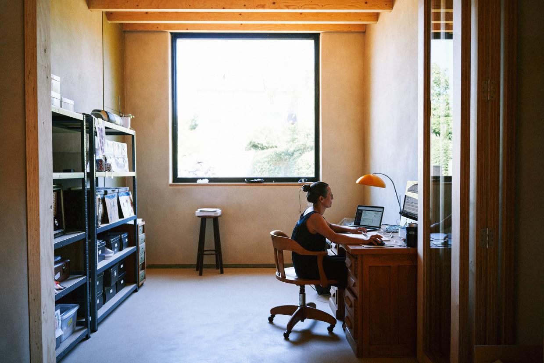 Een vrouw aan het werk in haar thuisbureau. 'Het is belangrijk dat telewerk een middel blijft om goed werk te leveren, het mag geen doel op zich worden', zegt arbeidspsycholoog Lode Godderis (KU Leuven). Beeld Thomas Sweertvaegher