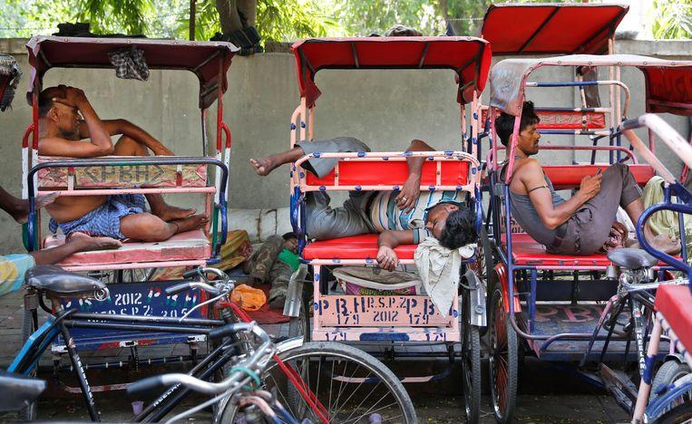 Riksja-chauffeurs in New Delhi rusten bij temperaturen rond de 48 graden. Beeld AP