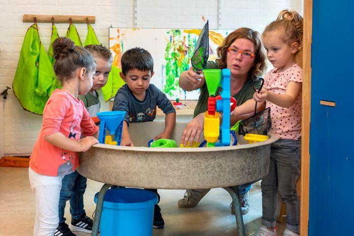Pedagogisch medewerker Loes Bierman in de weer met peuters tijdens de Zomerschool in de Lammerts van Buerenschool in Zetten.