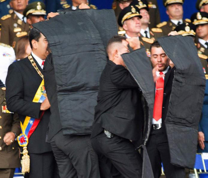 President Maduro wordt na de explosies snel afgeschermd door veiligheidsmedewerkers. De president lijkt aanvankelijk zelf niet goed te weten wat er precies is gebeurd.