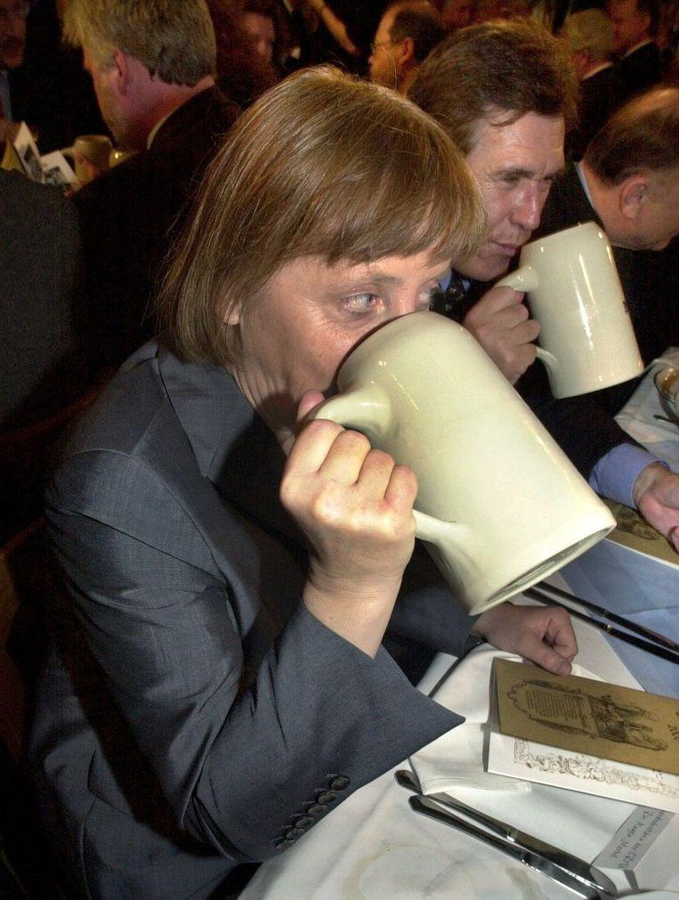 Merkel drinkt een liter bier tijdens het traditionele tapfeest in Nockherberg, München (foto stamt uit 2000). Beeld EPA