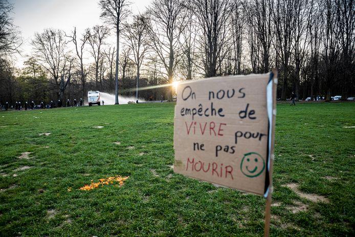 """""""On nous empêche de vivre pour ne pas mourir"""", lisait-on vendredi sur ce panneau au bois de la Cambre, avec une arroseuse en arrière-plan"""