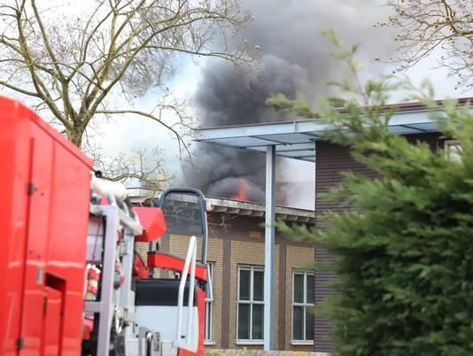 De vlammen slaan uit het dak van de voormalige school.