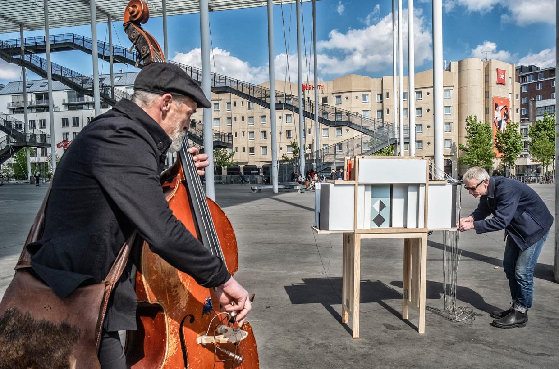 Kunstenaar Benjamin Verdonck en bassist Tomas De Smet entertainen voorbijgangers op het Theaterplein in Antwerpen. Beeld Tim Dirven
