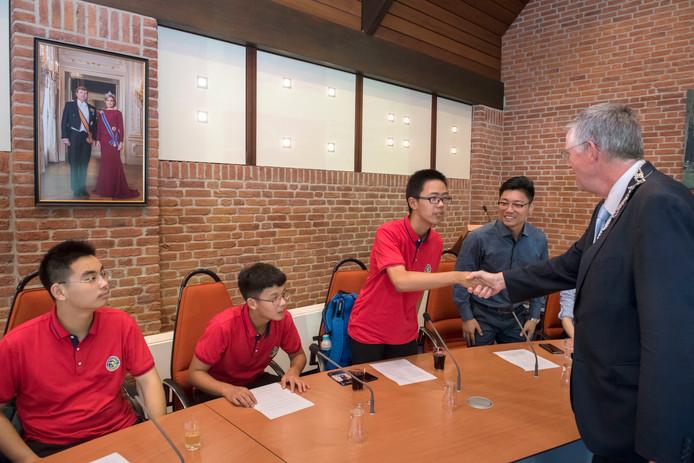 Burgemeester Baars (rechts) stelt zich voor aan de Chinese leerlingen.