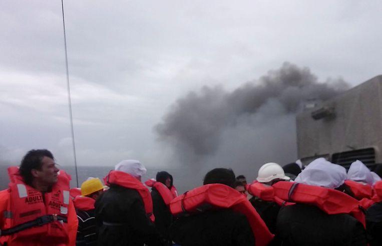 Passagiers van de veerboot wachten op redding nadat er brand is ontstaan. Beeld AP