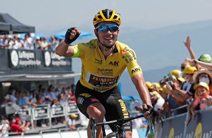 Primoz Roglic komt stralend over de finish op de Grand Colombier.