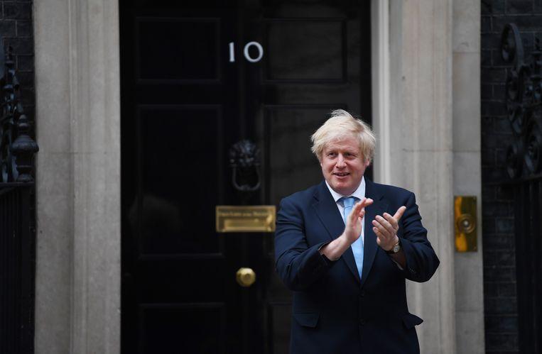 De Britse premier Boris Johnson klapt mee tijdens met het initiatief 'Clap For Our Carers'  van Annemarie Plas, 21 mei. Beeld Neil Hall / EPA