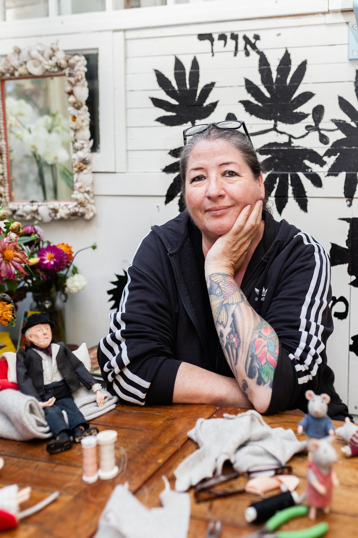 Karina Schaapman in haar loofhut, gemaakt van gebruikte kozijnen en afvalhout. 'Het is ons paradijsje.' Beeld Nina Schollaardt