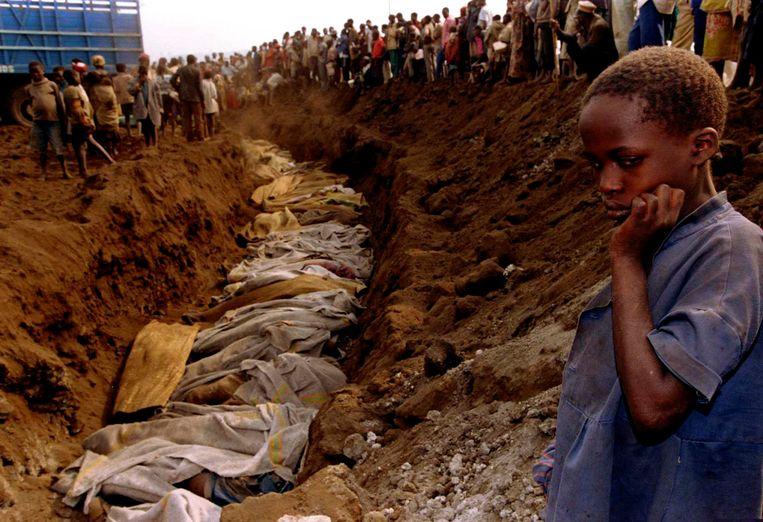 Een Rwandees meisje aan een massagraf in juli 1994 Beeld REUTERS