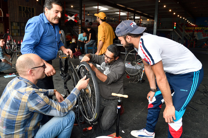 Salim (blauw overhemd) grijpt in bij de fiets van Saïd (grijze hoodie). Vrijwilliger Rik en tolk Samer helpen.