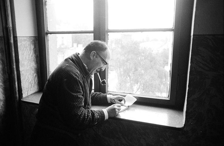 Igor Cornelissen met pijp, schrijvend voor een raam. Beeld Hollandse Hoogte / Hans van den Bogaard