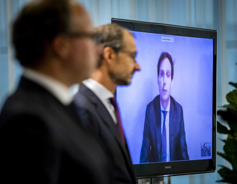 De ministers Wouter Koolmees (SZW), Eric Wiebes (EZK) en via een videoverbinding Wopke Hoekstra (Financiën) staan de pers te woord over het steun- en herstelpakket voor de economie.  Beeld ANP