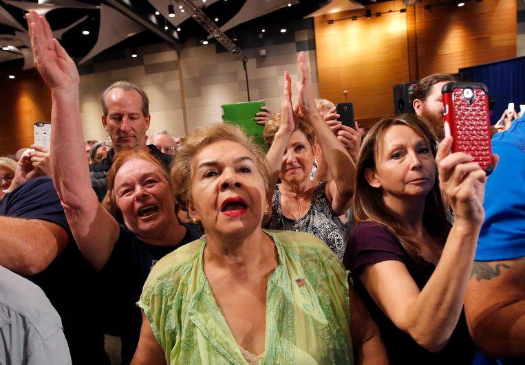 Aanhangers van Trump begroeten de miljardair zaterdag tijdens een drukbezochte bijeenkomst in Phoenix. Beeld ap