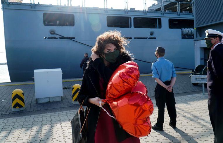 Een vrouw wacht haar familieleden op die zojuist zijn gearriveerd met een schip van de Duitse Marine in Wilhemshaven, op 17 september 2020.  Beeld AFP