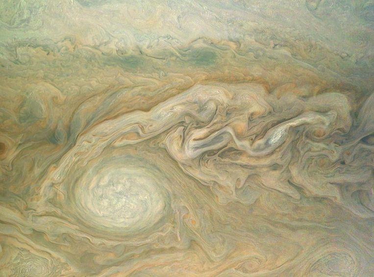 Een kleine wervelstorm veroorzaakt golfpatronen in de wolkenbanden van Jupiter. Beeld AFP