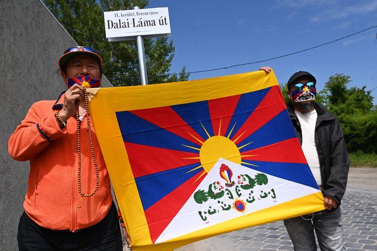 Activisten houden een Tibetaanse vlag omhoog bij de 'Dalai Lamastraat' in Boedapest. Beeld Attila Kisbenedek / AFP