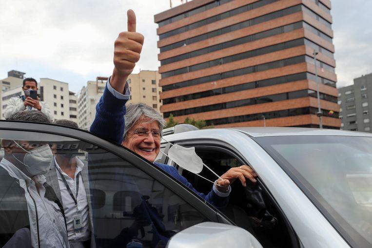 De rechtse kandidaat Guillermo Lasso groet zijn aanhang na een vergadering op het kantoor van de Nationale Kiesraad. Beeld EPA