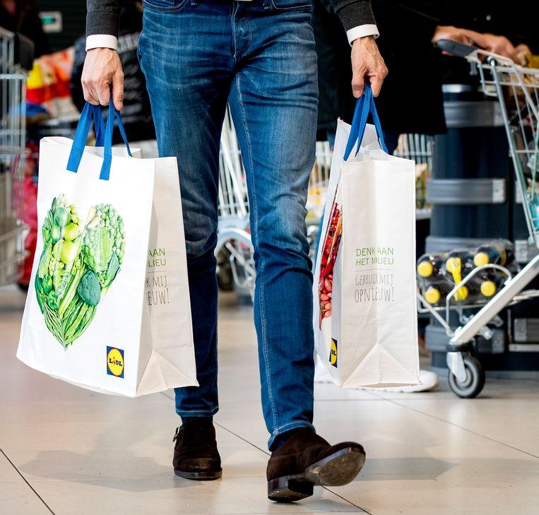 Wie naast zijn uitkering een tas boodschappen aanneemt van familie of vrienden kan daarvoor beboet worden. Beeld Hollandse Hoogte /  ANP