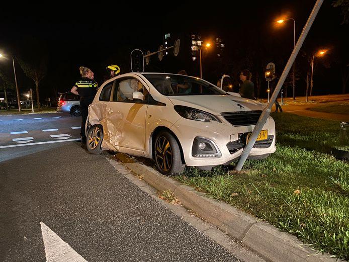 De witte auto ramde een verkeersbord.