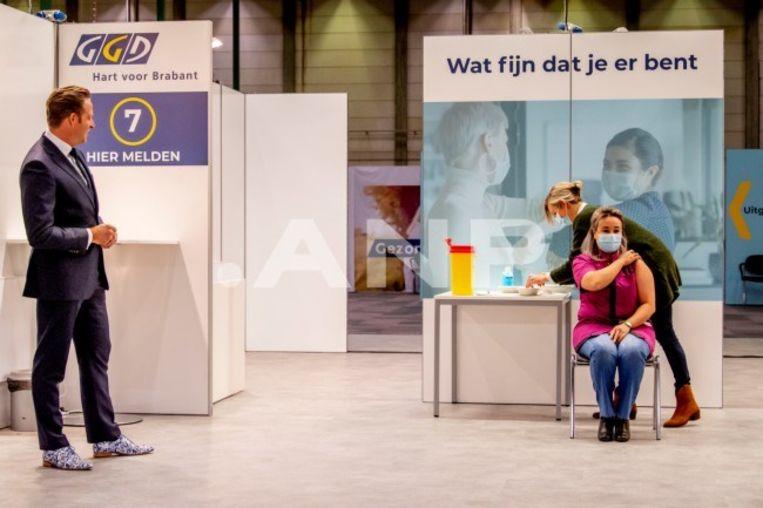 Verpleeghuismedewerker Sanna Elkadiri krijgt op 6 januari in het Brabantse Veghel als eerste Nederlandse het Pfizer-vaccin  toegediend, onder toeziend oog van minister Hugo de Jonge. Beeld ANP