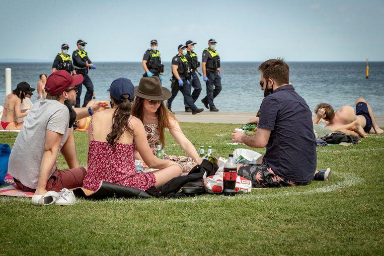 Badgasten picknicken onder het oog van de politie op St. Kilda-strand in Melbourne.  Beeld Darrian Traynor / Getty Images