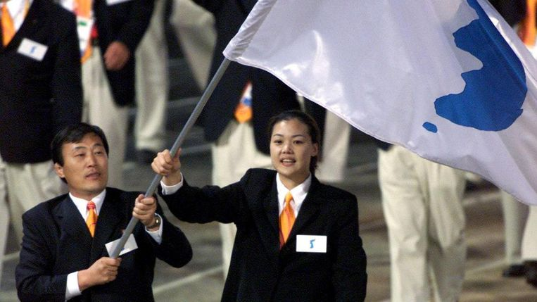 De vlagdragers, een uit Noord-Korea en een uit Zuid-Korea houden de gezamenlijke vlag vast. Beeld reuters