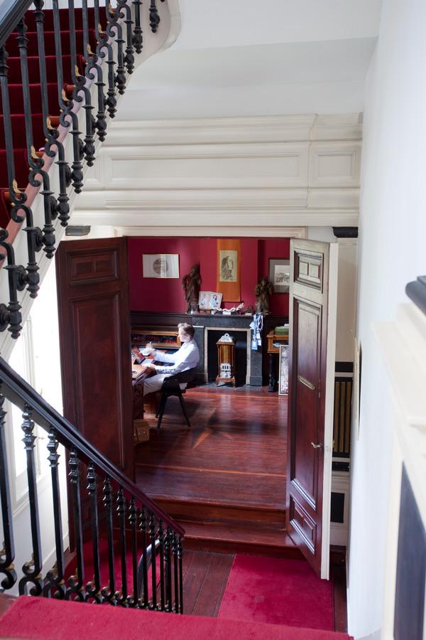 Het roodbruine hout geeft een koloniale toets aan het bureau van Vincent.