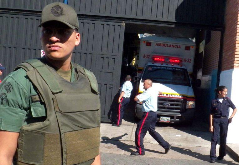 Archiefbeeld. Een Venezolaanse politieagent houdt de wacht voor de gevangenis van San Cristobal.  Beeld EPA