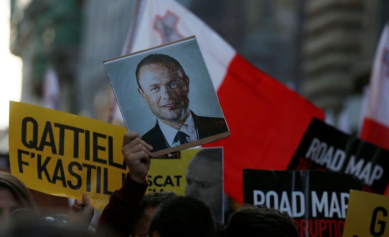 Een betoger houdt een foto de lucht in van een half onder het bloed bedekte Joseph Muscat, toen – in 2019 – nog eerste minister van Malta.  Beeld REUTERS