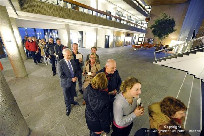 Burgemeester Theo Schouten houdt de wachtende stemmers gezelschap.