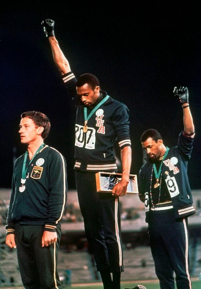 Het beroemdste podiumprotest ooit: Tommie Smith (m) en John Carlos (r) maken het black power-gebaar op de Spelen van 1968. De twee Amerikanen werden ervoor geschorst.
