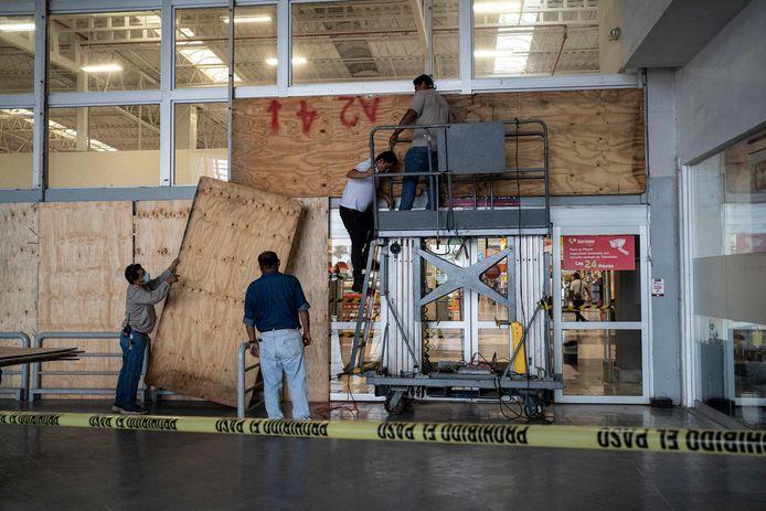 Voor de ramen van een supermarkt in Boca del Rio, Veracruz, worden ter bescherming dikke houten panelen geplaatst.