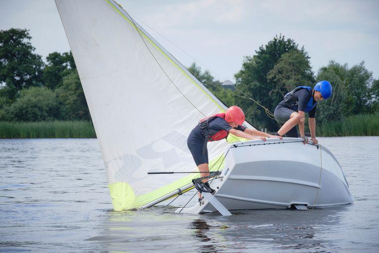 Een windstille dag bij zeilkamp Pean staat in teken van zeiltechnieken. Twee jongens proberen op het meer bij zeilschool hun boot expres om te laten slaan zonder zelf nat te worden. Beeld Sjaak Verboom