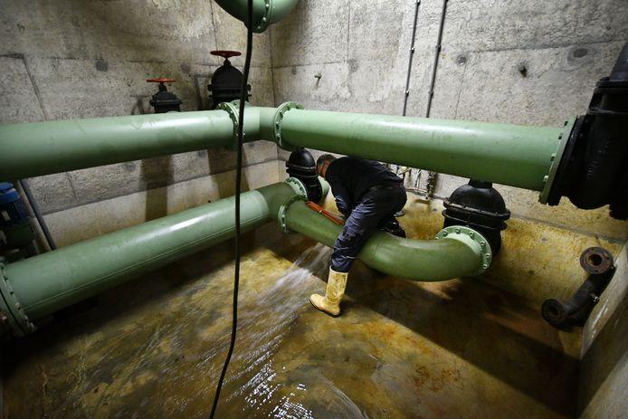 Een medewerker van Vitens laat vervuild water uit een van de vier bassins van het drinkwaterreservoir op de Tankenberg stromen.