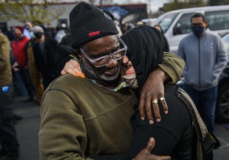 Charles McMillan (l) en Genevieve Hansen, twee getuigen in de zaak tegen de Amerikaanse politie-agent Derek Chauvin, omhelzen elkaar. Beeld AFP
