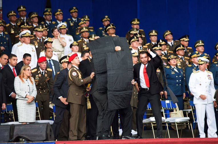 Op andere beelden is te zien hoe Maduro na een korte stilte wordt omringd door bodyguards die zwarte, waarschijnlijk kogelwerende, schermen omhoog houden.  Beeld AP