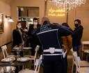 Een Italiaanse politieagent in gesprek met de eigenaren van restaurant Agrodolce in Rome. Het restaurant ging vorige week open, terwijl er een lockdown geldt voor de horeca.