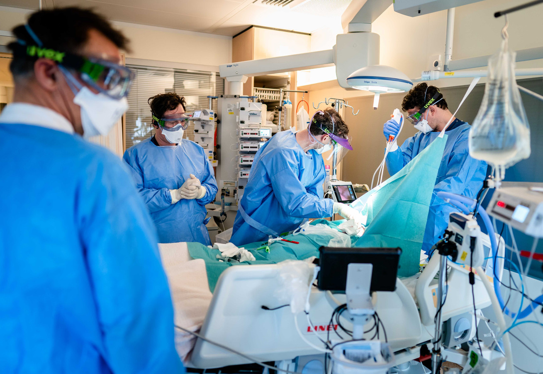 Medewerkers leggen een tracheotomie zodat de patiënt kunstmatig beademd kan worden op de speciale Covid-IC afdeling .