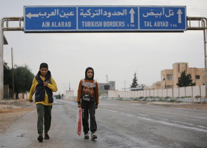 Syrische jongens lopen over een verlaten weg die naar de grensstad Tal Abyad leidt.