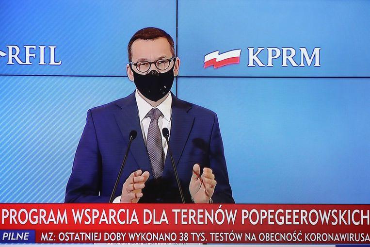 De Poolse premier Mateusz Morawiecki geeft tekst en uitleg bij de coronamaatregelen. Beeld EPA