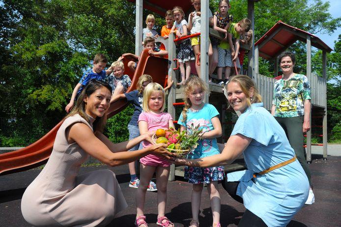 Latoya  Beekmans geeft Marthe, Jane en Inge (vlnr) van de kinderopvang in Koudekerke de mand met fruit