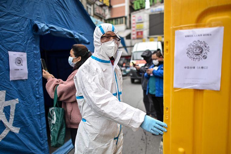 Een man in beschermende kledij voert controles uit bij de heropening van een markt in Wuhan, waar het coronavirus enkele maanden geleden uitbrak.   Beeld AFP