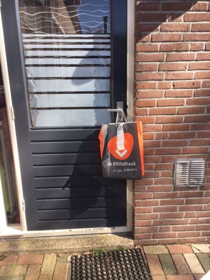 Medewerkers hangen de boeken in een tas aan de voordeur om fysiek contact te vermijden.
