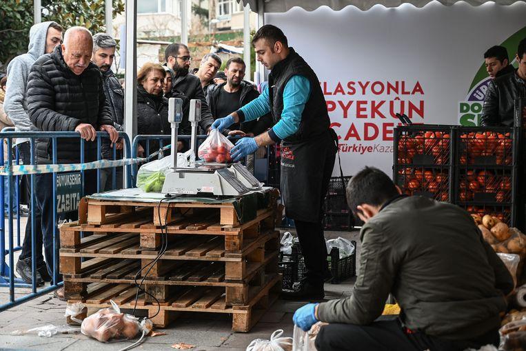 Mensen in de rij bij een tent van de gemeente Istanbul, waar tegen lage prijzen groente en fruit kunnen worden gekocht. Beeld AFP