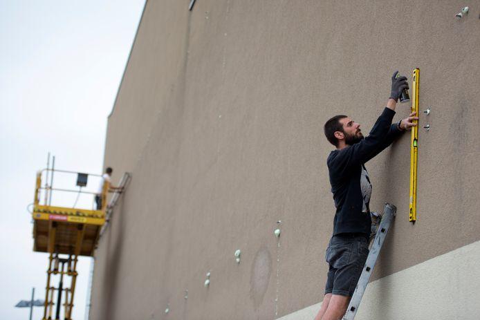Terwijl kunstenaar Robin Nas begonnen is met de voorbereidingswerkzaamheden voor zijn muurschildering (mural), wordt een oude lijst gedemonteerd (achtergrond).