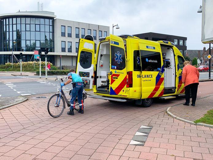 Terwijl de ambulancebroeder de fiets in de ambulance legt, neemt de vrouw via de zijkant plaats op een stoel.