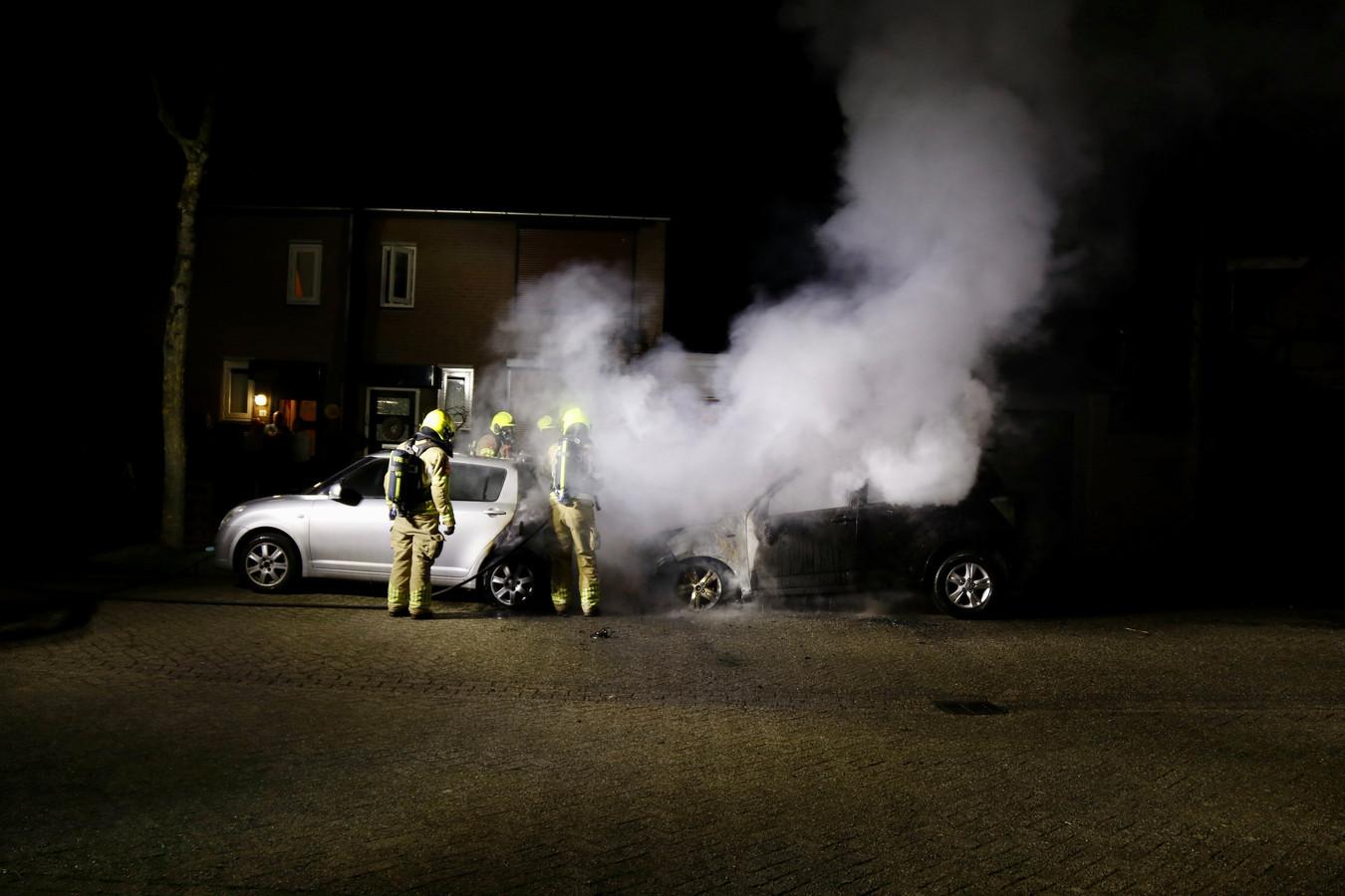 De brandweer blust twee brandende auto's aan de Spechtstraat in Gennep.
