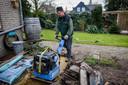 Jeroen Oosterik aan het werk met bestrating in een tuin.